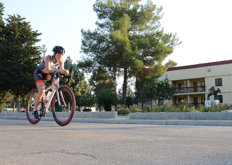 Tech. Sgt. Jessica Pigott, 717th Air Base Squadron logistics contract manager, bikes past the Hodja Inn during a sprint triathlon, Aug. 9, 2014, Incirlik Air Base Turkey. The triathlon consisted of a 5 kilometer run, 19 kilometer bike ride and 200 meter swim. (U.S. Air Force photo by Staff Sgt. Veronica Pierce/Released)
