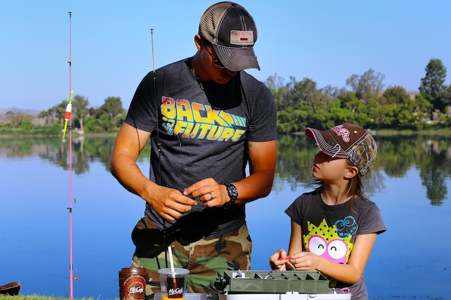 """Nathaniel Houck, and his daughter Alexandera, 9, prepare their hooks while competing in the 9th annual Lake O'Neill Kids Fishing Derby, here, Sept. 6.  The fishing derby is a competition where children attempt to catch the largest fish they can while competing in three to five, six to ten and eleven to fifteen age categories.  """"This event is designed to get kids out of the house where they can learn and have a fun outdoor experience,"""" said Dolores Perez, a recreation specialist with Marine Corps Community Services' Semper Fit division. """"I think this is a great way to keep them active and expose them to what could potentially be a new hobby."""""""