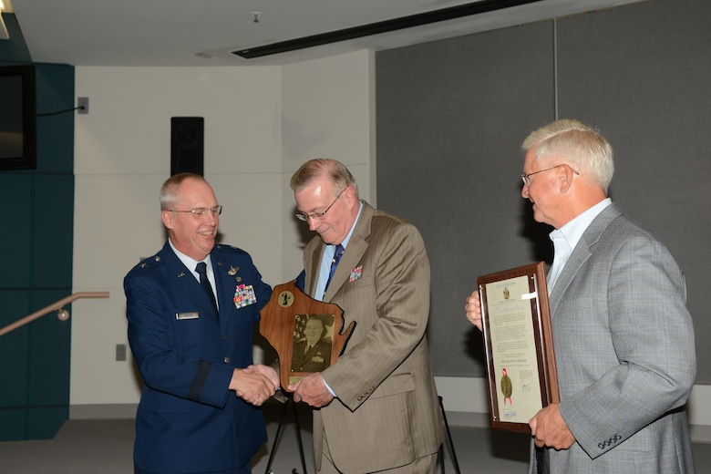 Retired Brig. Gen. Gerald C. Olesen receives the Wisconsin Air National Guard Hall of Fame induction award from Brig. Gen. Gary Ebben, assistant adjutant general for Air, during a Sept. 6 ceremony at Joint Force Headquarters, Madison, Wis. Retired Maj. Gen. Al Wilkening, former Wisconsin adjutant general, was by his side during the presentation. (Air National Guard photo by 1st Lt. Matthew Wunderlin)
