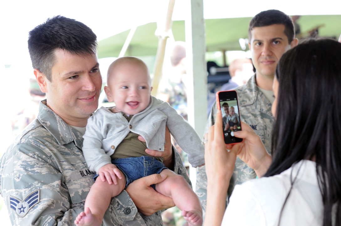 US Air Force Senior Airmen Thomas Blake pose for a photo with his child at Hancock Field in Syracuse, NY on Sept. 6, 2014. Blake and family attended the 174th Attack Wing's family day where military members and their family spent the afternoon enjoying, food, games and music at this annual event. (US Air Force Photo by New York Air National Guard Tech. Sgt. Justin A. Huett)