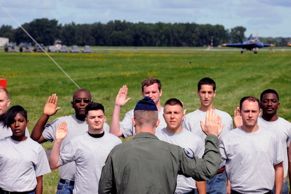 Col. Philip R. Sheridan, 127th Wing commander, swears in more than a dozen people as new members of the Michigan Air National Guard during a ceremony at the 2014 Selfridge Open House & Air Show, Sept. 6, 2014. The new Airmen will serve in various capacities in the 1,700-member 127th Wing, which is based at Selfridge Air National Guard Base, Mich. (U.S. Air National Guard photo by Master Sgt. David Kujawa)