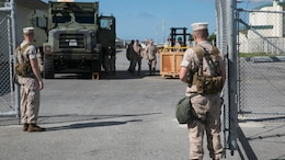 Marines stand guard at a warehouse during exercise Ulchi Freedom Guardian Aug. 22 at Camp Kinser. The Marines are training for real combat situations in the Asia-Pacific region by checking for security badges, security access levels and searching all bags entering the grounds. The Marines are with 3rd Marine Logistics Group, III Marine Expeditionary Force.