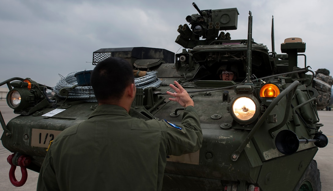 Staff Sgt. Quan Vu, 7th Airlift Squadron loadmaster, instructs Army Private 1st Class Austin Hurrelbrink, 2nd Cavalry Regiment soldier, on proper procedures of loading a Stryker into a C-17 Globemaster III in support of Steadfast Javelin II on Ramstein Air Base, Germany, Sept. 2, 2014. (U.S. Air Force photo/Senior Airman Damon Kasberg)