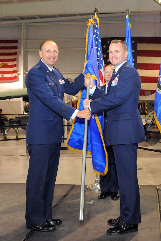 Brig. Gen. Carl A. Buhler assumes command of the Ogden Air Logistics Complex during a change of command ceremony Monday at Hill Air Force Base. From right, Buhler receives the ALC guidon from Lt. Gen. Bruce A. Litchfield, Air Force Sustainment Center commander, who presided over the ceremony while Chief Master Sgt. Robert B. Dodd, Ogden ALC superintendent, looks on. (U.S. Air Force photo by Todd Cromar)