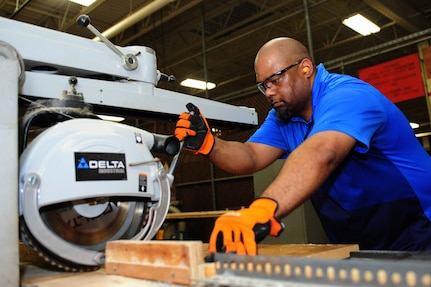 Darryl Jordan, 633rd Logistics Readiness Squadron wood worker, uses a radial arm saw to cut pieces of wood at Langley Air Force Base, Va., Sept. 3, 2014. Jordan builds crates and pallets used to move cargo. (U.S. Air Force photo by Airman 1st Class Areca T. Wilson/Released)