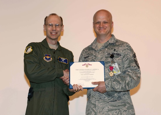 Maj. Gen. Bart Iddins, 59th Medical Wing commander, presents the Legion of Merit to Chief Master Sgt. Jason Wagner Sept. 5, 2014, at the Wilford Hall Ambulatory Surgical Center Auditorium, Joint Base San Antonio-Lackland. Wagner earned the Legion of Merit for his outstanding contributions as the Health Services Management Career Field Manager, Air Force Medical Operations Agency, from June 6, 2009 to June 30, 2013. Established in July 1942, the Legion of Merit is presented for those who have demonstrated exceptionally meritorious conduct in the performance of outstanding services. (Photo altered for security purposes) (U.S. Air Force photo/Staff Sgt. Jerilyn Quintanilla)