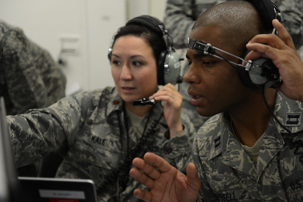 U.S. Air Force Maj. Carol Kale, 606th Air Control Squadron assistant director of operations and native of Fort Worth, Texas, left, and U.S. Air Force Capt. Romaine Russell, 606th ACS bravo flight commander and native of Baltimore, relay information during a simulation inside a battle-space command control center Aug. 18, 2014 at Spangdahlem Air Base, Germany. These operators maintain a real-time picture of the area of operations while communicating with air and ground assets. The constant training 606th ACS Airmen undergo allows them to be ready to deploy at a moment's notice. (U.S. Air Force photo by Senior Airman Gustavo Castillo/Released)