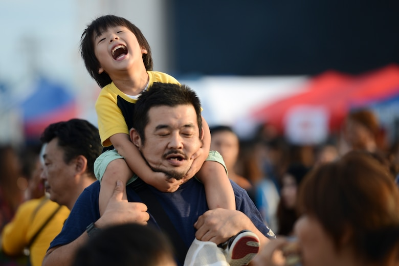A boy plays with his father during the 2014 Japanese-American Friendship Festival at Yokota Air Base, Japan, Sept. 7, 2014. Yokota, with an average populace of 11,000 people, hosted more than 148,000 during the two-day festival. (U.S. Air Force photo by Staff. Sgt. Cody H. Ramirez/Released)