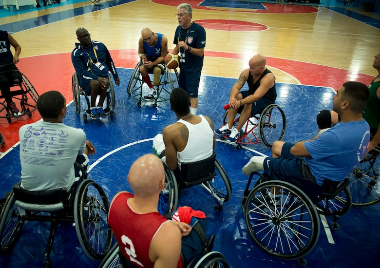 Grant Moorhead, the U.S. team's wheelchair basketball coach, gives instructions to the players during practice for the first Invictus Games Sept. 8, 2014, in London. Wounded warriors from the U.S. and 13 other nations came together here Sept. 8 to participate in their first team training for the paralympic-style events, including swimming, track and field, seated volleyball, wheelchair basketball, and wheelchair rugby, among others.(U.S. Air Force photo/Staff Sgt. Andrew Lee)