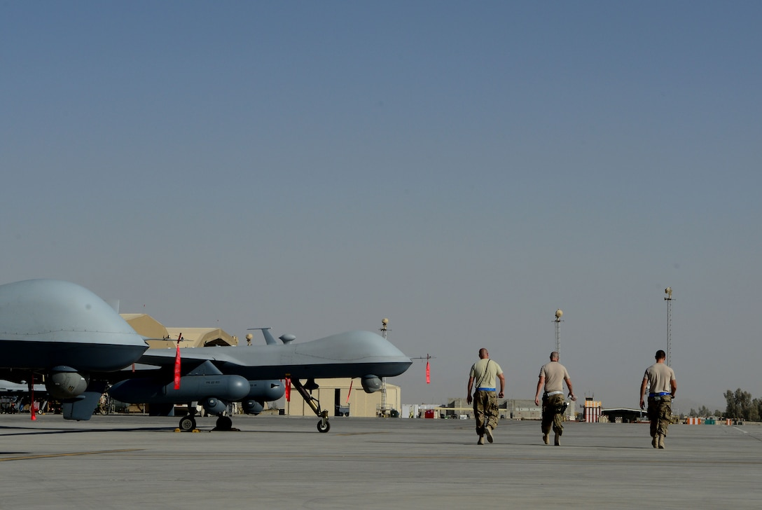 Aircraft armament systems specialists walk past MQ-9 Reapers with the 62nd Expeditionary Reconnaissance Squadron Aug. 18, 2014, at Kandahar Airfield, Afghanistan. The Reaper is launched, recovered and maintained here. It is also remotely operated by pilots in bases located in the U.S. The Airmen are with the 451st Expeditionary Aircraft Maintenance Squadron. (U.S. Air Force photo/Staff Sgt. Evelyn Chavez)