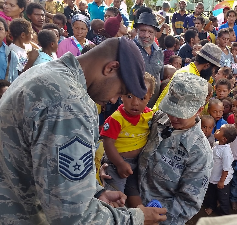 Master Sgt. Jamain Braxton, the anti-terrorism officer for Pacific Unity 14-8 deployed from Andersen Air Force Base, Guam, tries a pair of shoes on a child during a shoe drive for the local community of Mount Hagen, Papua New Guinea, Sept. 8, 2014. While deployed in support of Pacific Unity Braxton organized the shoe drive to benefit children in the community. Pacific Unity helps cultivate common bonds and foster goodwill between the U.S. and regional nations through multilateral humanitarian assistance and civil military operations. (U.S. Air Force photo by Airman 1st Class Jaimie Aquino/Released)