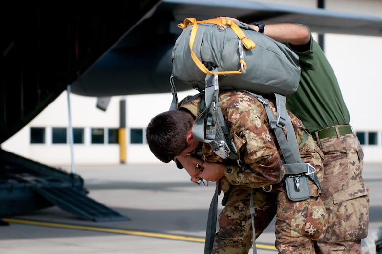 Italian Army Cpl. Felerico Yagliaroll of the 186th Parachute Regiment receives assistance with his gear from a fellow Italian Soldier as he prepares to board a Kentucky Air National Guard C-130 Hercules aircraft at Ramstein Air Base, Germany, Sept. 5, 2014, during Operation Saber Junction. Yagliaroll's unit is participating in the operation with troops from 17 NATO countries. (U.S. Air National Guard photo by 2nd Lt. James W. Killen/Released)