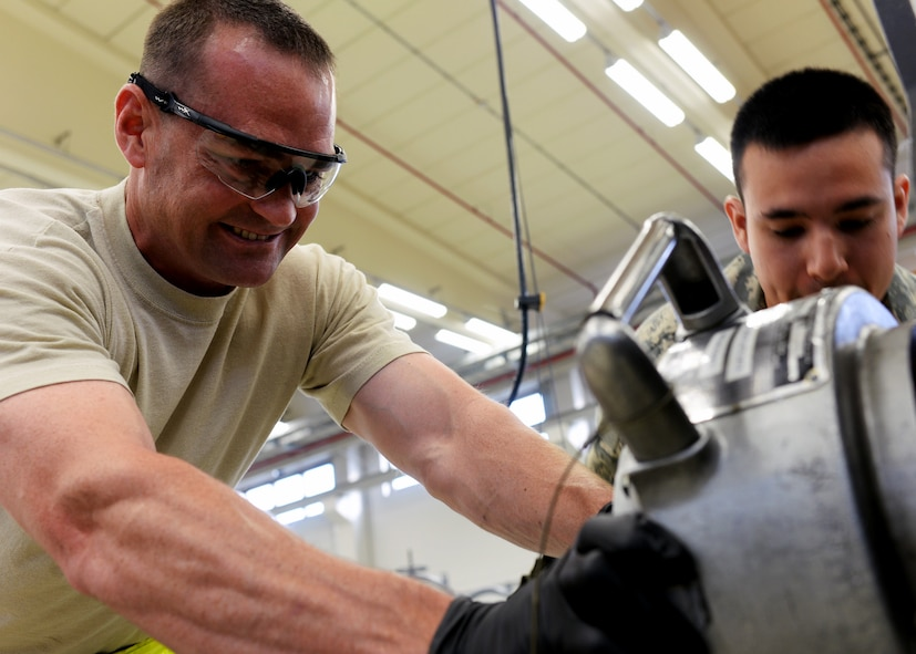 U.S. Air Force Tech. Sgt. Galen Perry, left, and Senior Airman William Schaumann, 52nd Component Maintenance Squadron aerospace propulsion technicians from San Antonio, N.M., and Batesville, Ark., respectively, detach a component of a jet engine piece in the propulsion shop at Spangdahlem Air Base, Germany, Sept. 9, 2014. The 52nd CMS is divided into different crews which work on different mechanical components. (U.S. Air Force photo by Airman 1st Class Timothy Kim/Released)