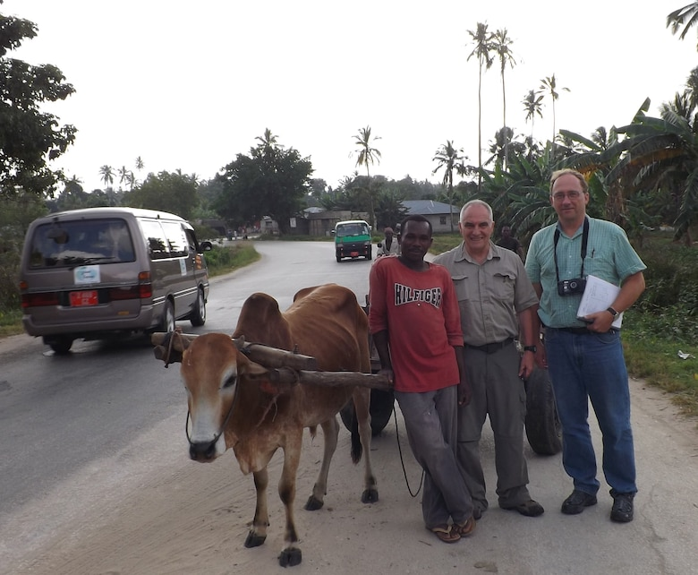 An oxen cart is one mode of transportation in Tanzania and one of the local drivers stops and takes a picture with Patrick Chauvey, chief of environmental programs, Fort Benning, Ga., and Danny Klima, civil engineer, Omaha District USACE.