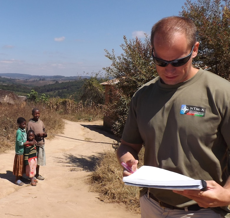 Robert Lawrence, civil engineer Philadelphia District USACE compiles his notes during an assessment of the roads in Tanzania while local children look on.