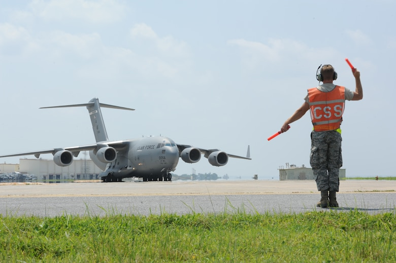 U.S. Air Force Staff Sgt. Nicholas Otos, 733rd Air Mobility Squadron avionics technician craftsman, marshals a C-17 Globemaster III into its spot on the flight line for inspection and servicing on Kadena Air Base, Japan, Sept. 9, 2014. The 733rd AMS aircraft maintenance unit maintains multiple airframes on Kadena to ensure aircraft are mission ready at all times. (U.S. Air Force photo by Airman 1st Class Zackary A. Henry)