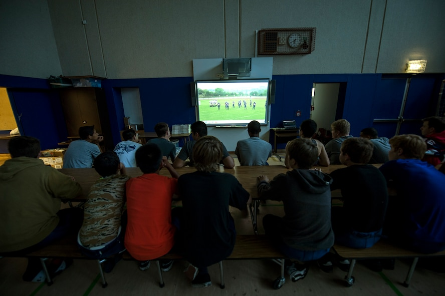 Bitburg Barons football players watch game film prior to the start of their season opener game against the Baumholder Buccaneers Sept. 6, 2014, at Bitburg Annex, Germany. The team plays five games during the course of the regular season. (U.S. Air Force photo by Senior Airman Rusty Frank/Released)