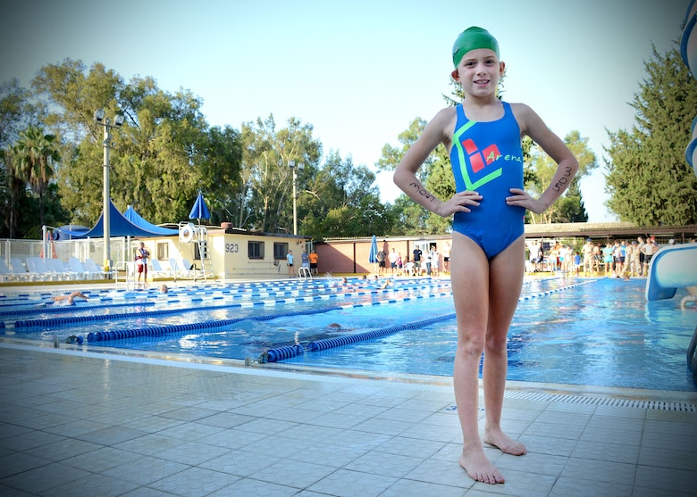 Kassey Daugherty, 8, poses in front of a swimming pool after completing a five kilometer run and 200-meter swim during a sprint triathlon Aug. 9, 2014, Incirlik Air Base, Turkey. Kassey is the daughter of Tech. Sgt. Kenneth Daugherty, 39th Communications Squadron commander's programs section chief. Daugherty and his family use pillars of resilience such as U.S. Air Forces in Europe and Air Forces Africa's RU Fit program. (U.S. Air Force photo by Staff Sgt. Veronica Pierce/Released)
