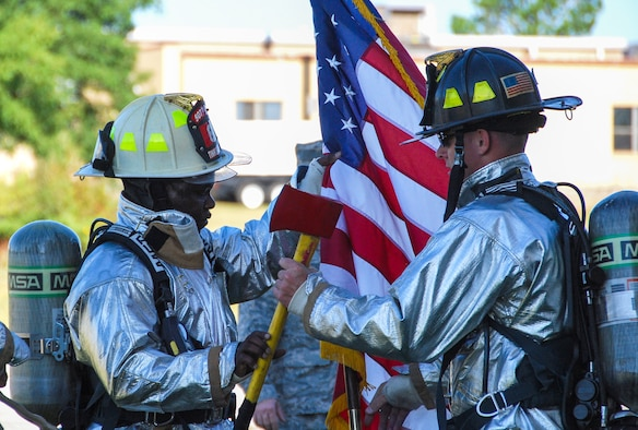Firefighters from the 507th Civil Engineer Squadron trade the U.S. flag and an axe during the 5th annual fire climb Sept. 7, 2014, at the fire training tower at Tinker Air Force Base, Okla. The axe and flag were pieces of several packs carried up and down the tower stairs as members of the CES and the wing climbed the equivalent of 110 stories to commemorate the 343 firefighters, emergency medical technicians and paramedics who lost their lives during the 9/11 attacks on the World Trade Centers. (U.S. Air Force photo/Senior Airman Krystin Trosper)