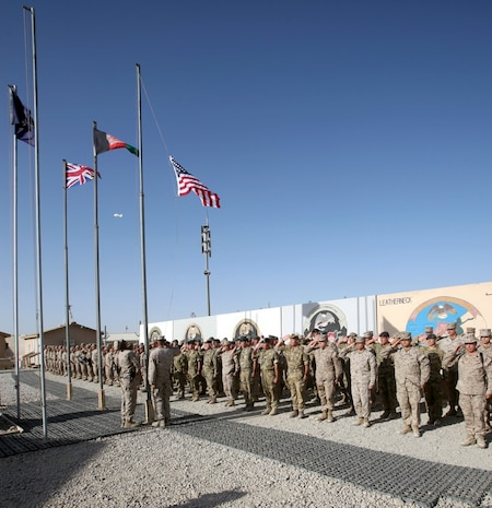 """Marines, sailors and coalition partners with Regional Command (Southwest) salute while the American flag is raised at the RC(SW) headquarters during a 9/11 memorial ceremony aboard Camp Leatherneck, Afghanistan, Sept. 11, 2014. """"For Americans, 9/11 evokes a very special meaning. It's a memory of the world as we knew it on that day changing forever. Today's simple but solemn ceremony is a tribute to those innocent young men, women and children who were killed by a cowardly and heartless act of terror,"""" said Brig. Gen. Daniel D. Yoo, commander, RC(SW) and Marine Expeditionary Brigade – Afghanistan."""