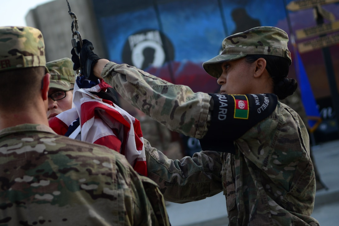 U.S. Air Force Staff Sgt. Talisa Williams, 455th Expeditionary Force Support Squadron, lowers a U.S. flag during a retreat ceremony at Bagram Airfield, Afghanistan Sept. 11, 2014.  Airmen participated in a Patriot's Day Retreat and reenlistment ceremony Sept. 11, 2014.  Patriot's Day is an annual observance to remember those who were injured or died during the attacks on Sept. 11, 2001. (U.S. Air Force photo by Staff Sgt. Evelyn Chavez)