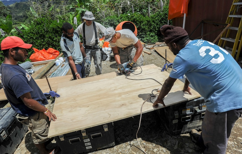 Members of the 154th Civil Engineer Squadron partner with day laborers from the local community to cut pieces of wood for a basketball backboard  Sept. 8, 2014, during Pacific Unity 14-8 in Mount Hagen, Papua New Guinea. Pacific Unity is a bilateral Engineering Civic Action Program conducted in the Asia-Pacific region in collaboration with host nation civil authorities and military service members that build upon previous engagements and exercises, and continue to mature U.S. and Asia-Pacific civil-military interoperability. The Airmen are deployed from the Hawaii Air National Guard. (U.S. Air Force photo/Tech. Sgt. Terri Paden)