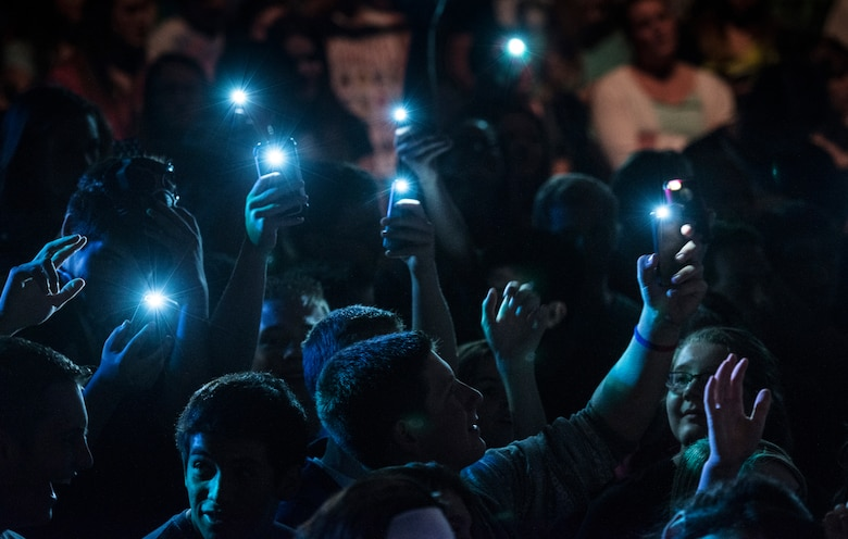"Audience members hold up cell phones with the flashlights turned-on during a performance by U.S. Air Force Band of the Golden West rock ensemble ""Mobility"" at Twin Falls High School in Twin Falls, Idaho, Sept. 9, 2014. (U.S. Air Force photo by Tech. Sgt. Samuel Morse/Released)"