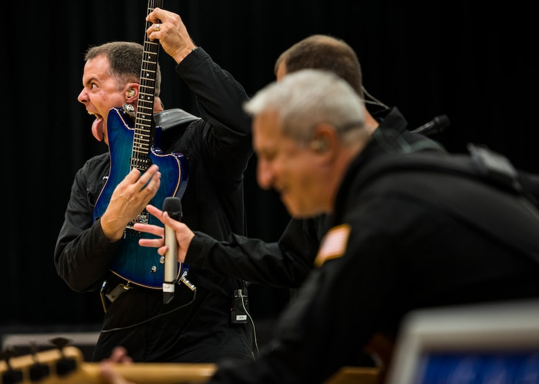 "Master Sgt. Dennis Pack, lead electric guitarist for U.S. Air Force Band of the Golden West rock ensemble ""Mobility,"" rocks-out on a guitar riff while making a face reminiscent of 80s hair bands during a performance at Mountain Home High School in Mountain Home, Idaho, Sept. 8, 2014. Showmanship is a big part of the band's performance, allowing the members to use their own personal style to have fun and engage the audience. (U.S. Air Force photo by Tech. Sgt. Samuel Morse/Released)"
