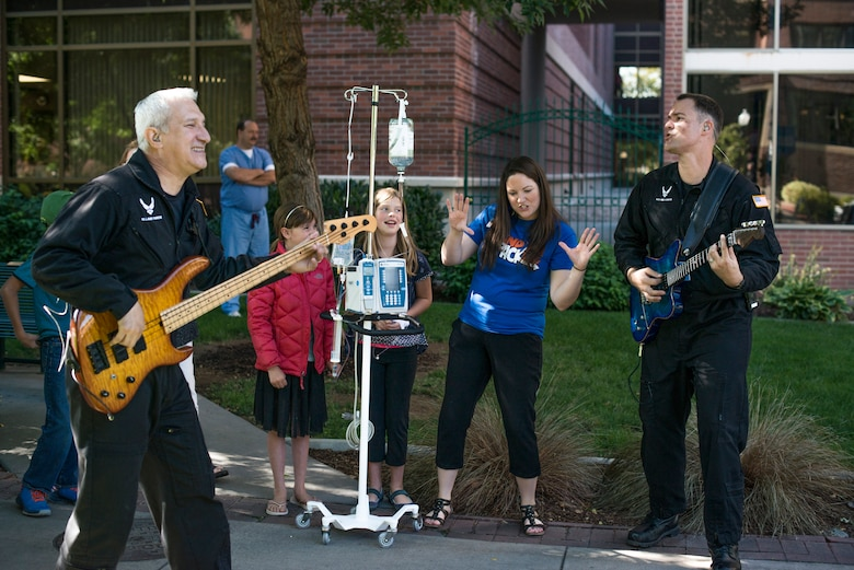 U.S. Air Force Master Sgts. Douglas Tejada and Dennis Pack play a song in the crowd at St. Luke's Children's Hospital in Boise, Idaho, Sept. 5, 2014. Mobility is a subdivision of  the U.S. Air Force Band of the Golden West, which played numerous sets all around southern Idaho during their six-day tour. (U.S. Air Force photo by Airman 1st Class Brittany A. Chase/Released)