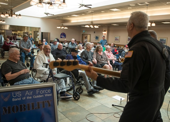 U.S. veterans watch as U.S. Air Force Master Sgt. Douglas Tejada plays bass guitar during a song at the Idaho State Veteran's Home, Sept. 4, 2014. Mobility played numerous sets all around southern Idaho during their six-day tour. (U.S. Air Force photo by Airman 1st Class Brittany A. Chase/Released)