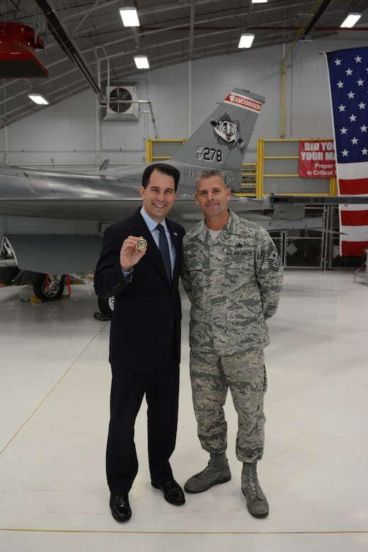 Governor Scott Walker, Wisconsin governor, shows off his new chief coin following a Sept. 11, 2001 remembrance ceremony in Hangar 406 at the 115th Fighter Wing in Madison, Wis., Sept. 11, 2014. Chief Master Sgt. Thomas Safer, 115 FW command chief, recently designed the new coin and chose Walker as the first recipient. (Air National Guard photo by Senior Airman Andrea F. Liechti)
