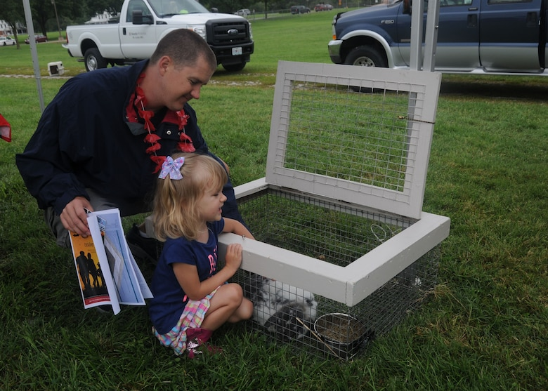 Senior Airman Ben Middleton,157th Air Operations Group, watches his daughter as she participates at the petting zoo organized by Purina Farms during the 2014 Family Picnic at Jefferson Barracks, Missouri on Sept. 6, 2014. Purina Farms also presented a dog show for Citizen Airmen and their Families at the event. (U.S. Air National Guard photo by Senior Airman Nathan Dampf)