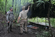 A student explains to medic Sgt. 1st Class Remo Soldaini, 1st Bn (Abn), 509th Inf Reg, how he and his team wove palm fronds and other natural materials into a rainproof shelter during a survival exercise held Aug. 30-Sept. 1 in the Atchafalaya Basin. (U.S. Army photo by Jean Dubiel)