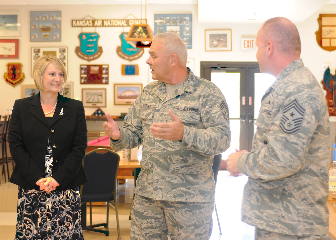 Marie Hotaling, Chief Master Sgt. Russ Brotsky, command chief of the 184th Intelligence Wing, and Chief Master Sgt. Jim Hotaling, Air National Guard command chief, engage in conversation during a visit to the 184th IW, McConnell Air Force Base, on Sept. 7, 2014. During the visit, Hotaling spoke at an enlisted all-call and visited Airmen in their work areas. Marie Hotaling was briefed on Kansas' Family Readiness Programs and spoke with 184th volunteers and family members. (U.S. Air National Guard photo by Tech. Sgt. Maria A. Ruiz)