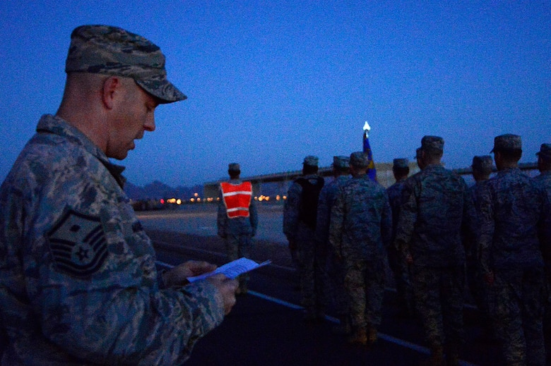 Master Sgt. Jason Maberry, 612th Air Communication Squadron (ACOMS) First Sgt., reads a description of American Airlines Flight 11 during the first stop of the 612th ACOMS memorial march around Davis-Monthan AFB, Ariz., Sept. 11, 2014. The squadron stopped at 8:46 a.m. (EST) as a remembrance of the first aircraft to hit the North Tower of the World Trade Center. (USAF photo by Staff Sgt. Heather Redman/Released)