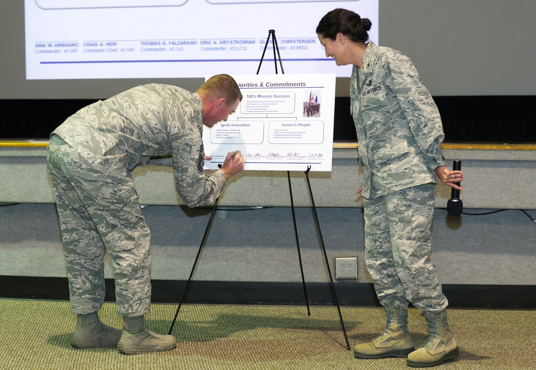 Brig. Gen. Nina Armagno, 45th Space Wing commander, looks on as Chief Master Sgt. Craig Neri, 45th SW command chief, adds his signature to the group commander's new priorities and commitments poster during the Commander's Call, Sept. 5, 2014, at Patrick Air Force Base, Fla. The vision and mission statements were changed only slightly, but the priorities and commitments were revised to better reflect where we are, where we want to go, what we already do well, and where we need work. (U.S. Air Force photo/Cory Long) (Released)