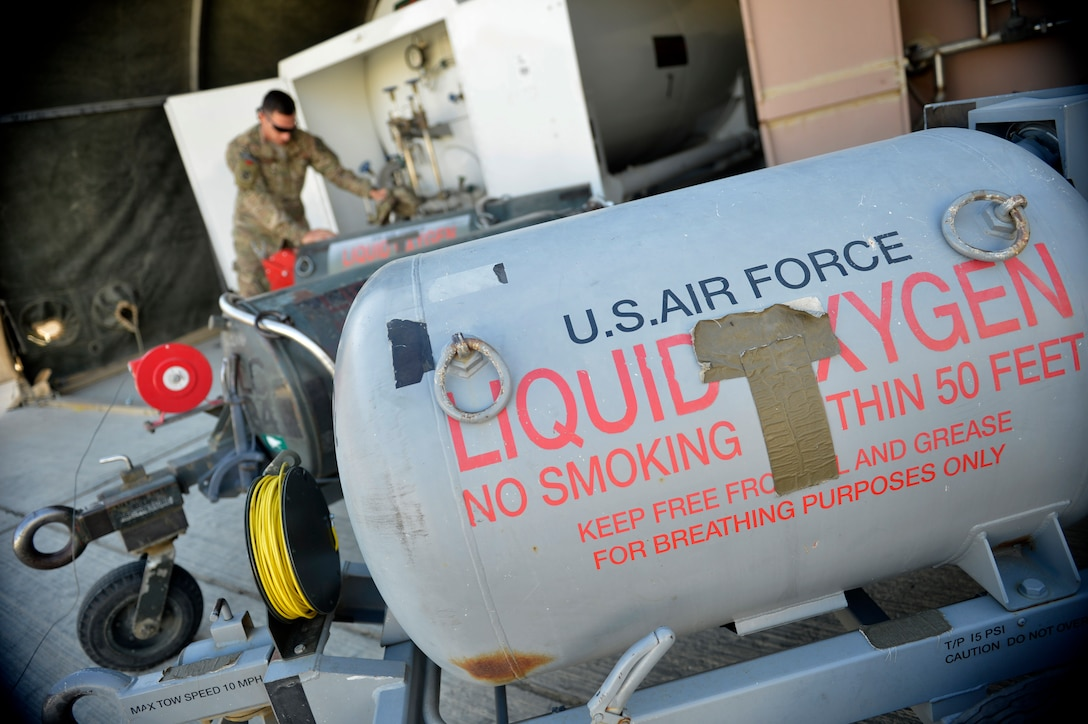A U.S. Air Force Airman from the 455th Expeditionary Logistics Readiness Squadron refills liquid oxygen carts at Bagram Airfield, Afghanistan Sept. 5, 2014. Cryogenic technicians work with extremely cold substances that boil at subzero temperatures then evaporate into breathable air. The cryogenics technicians support 6,000 aircraft missions and issue more than 4,000 gallons of liquid oxygen per month. (U.S. Air Force photo by Staff Sgt. Evelyn Chavez/Released)