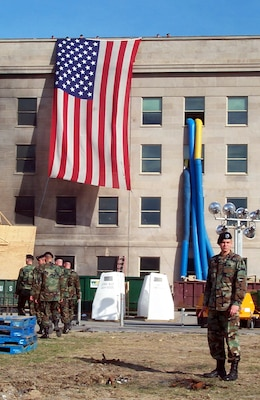 "Soldiers from A Company, 3rd Infantry -- ""The Old Guard"" -- prepare Oct. 11, 2001, to lower the garrison flag that draped the side of the Pentagon beside the impact site where terrorists crashed a hijacked airliner Sept. 11, 2001. The flag was ceremonially retired. DoD photo by Jim Garamone"
