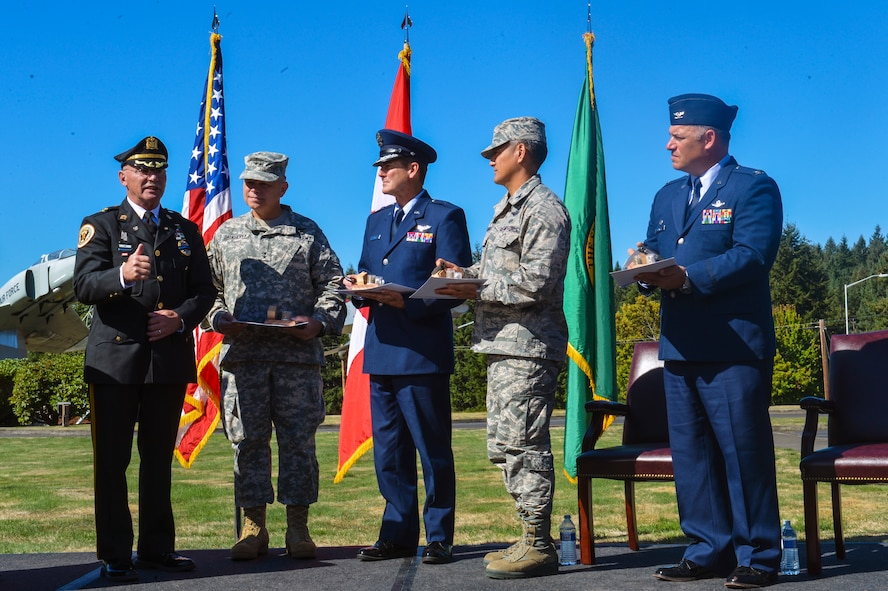 Far left, Steven Saymon, retired Brooklawn Police Department police inspector, presents gifts, symbolic to the 2001 attacks to, from left to right, Maj. Gen. Bret Daugherty, Washington National Guard Adjutant General, Brig. Gen. John Tuohy, Washington Air National Guard commander, Col. David Kumashiro, 62nd Airlift Wing commander and Col. Pete Stavros, Western Air Defense Sector commander. The gifts included a knife made of steel from the World Trade Center, soil from the Flight 93 crash site, and rubble stones from the Pentagon. (U.S. Air Force photo/Staff Sgt. Russ Jackson)