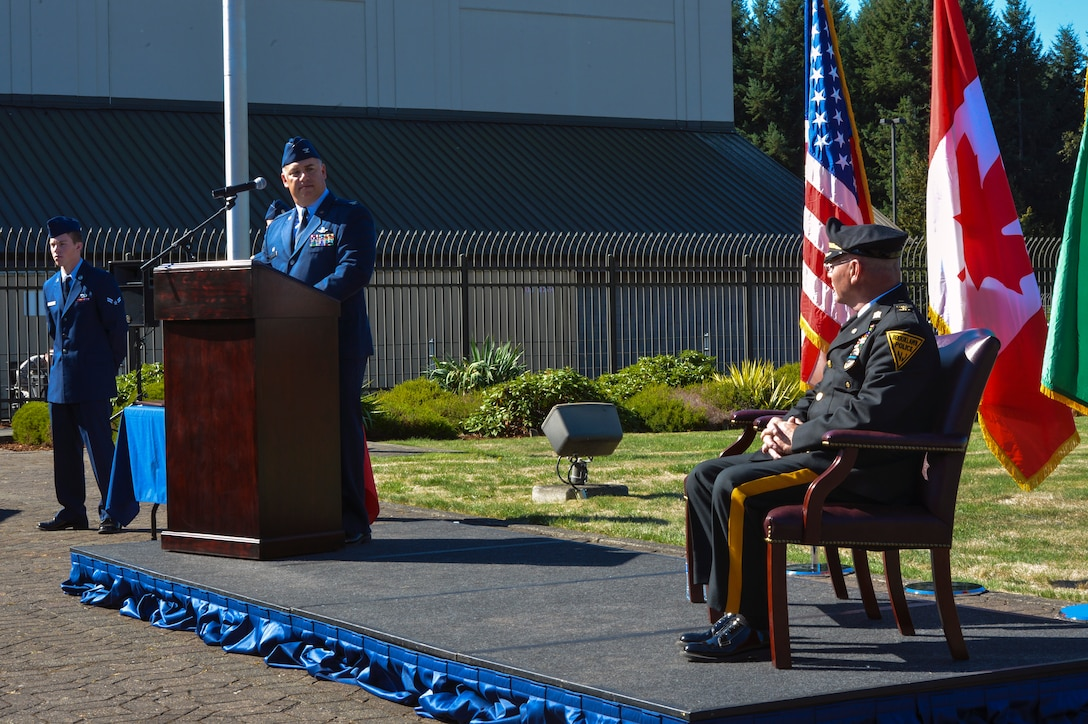 Col. Pete Stavros, Western Air Defense Sector commander, introduces Steven Saymon, retired Brooklawn Police Department police inspector, Sept. 11, 2014, during the WADS 9/11 memorial ceremony at Joint Base Lewis-McChord, Wash. During the 2001 attacks, WADS scrambled fighter aircraft from every base they could and set up air patrols over most of the major cities in America. (U.S. Air Force photo/Staff Sgt. Russ Jackson)