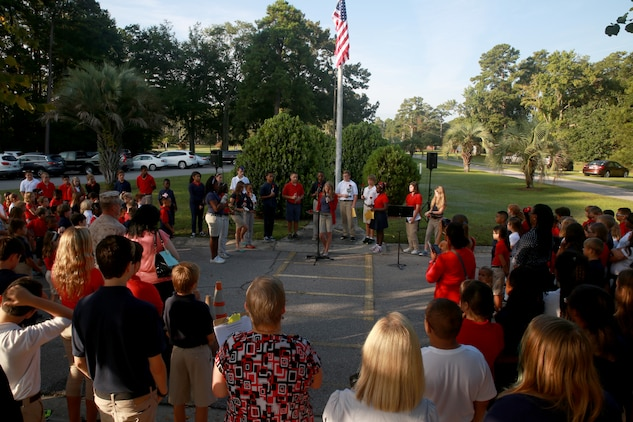 Students with Bolden Elementary/ Middle school aboard Laurel Bay Community Housing demonstrated their respect in remembrance of the 9/11 attacks on the United States, Sept. 11, 2014. The students retired an American flag and read student-produced poetry that acknowledged the sacrifices made 13 years before.