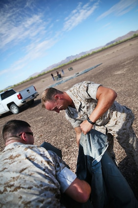 1st Lt. Stephen Shepard, Landing Support Company, Air Delivery platoon commander, packs away a Joint Precision Airdrop System parachute during testing of the system Aug. 26, 2014, at Yuma Proving Ground, Ariz. The JPADS systems use GPS, a modular autonomous guidance unit, or MAGU, a parachute and electric motors to guide cargo within 150 meters of their target points. To test its precision, the Marines used a series of palletized loads attached to parachutes with the GPS integrated system and dropped them from various heights.  (U.S. Marine Corps photo by Sgt. Laura Gauna/ released)