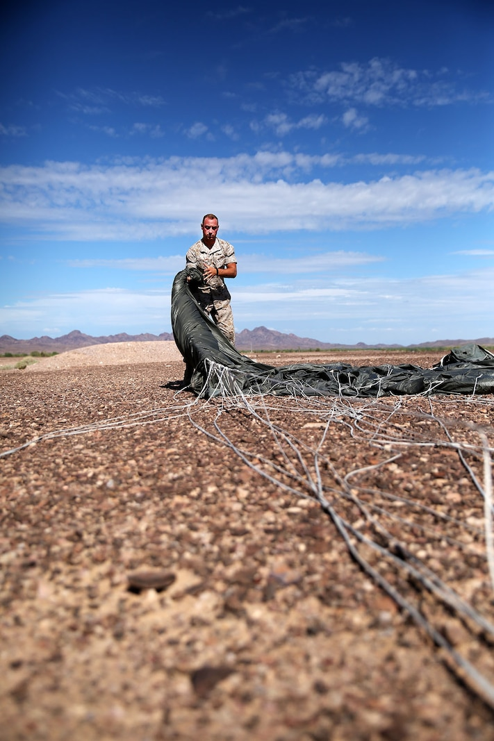 1st Lt. Stephen Shepard, Landing Support Company, Air Delivery platoon commander, folds a Joint Precision Airdrop System parachute during testing of the system Aug. 26, 2014, at Yuma Proving Ground, Ariz. The JPADS systems use GPS, a modular autonomous guidance unit, or MAGU, a parachute and electric motors to guide cargo within 150 meters of their target points. To test its precision, the Marines used a series of palletized loads attached to parachutes with the GPS integrated system and dropped them from various heights. (U.S. Marine Corps photo by Sgt. Laura Gauna/ released)