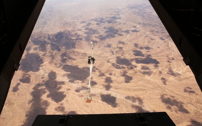 A Joint Precision Airdrop System drops from an MV-22 Osprey during testing of the system Aug. 26, 2014, at Yuma Proving Ground, Ariz. The JPADS systems use GPS, a modular autonomous guidance unit, or MAGU, a parachute and electric motors to guide cargo within 150 meters of their target points. To test its precision, the Marines used a series of palletized loads attached to parachutes with the GPS integrated system and dropped them from various heights. (U.S. Marine Corps photo by Sgt. Laura Gauna/ released)