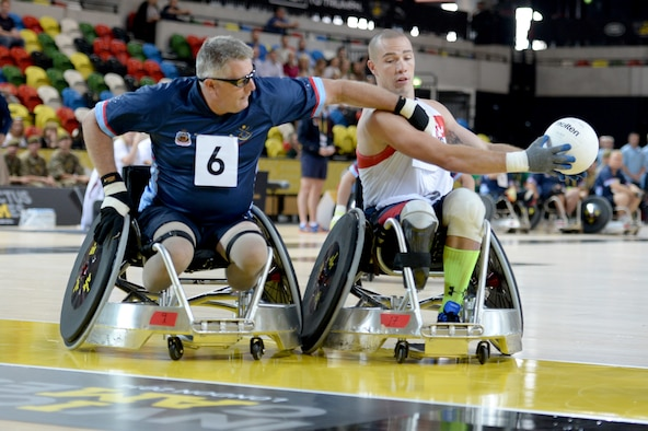 Army Sgt. Ryan McIntosh, representing the U.S., keeps the ball away from a defender during a wheelchair rugby match against Australia Sept. 12, 2014, at the 2014 Invictus Games in London. The U.S. won the match 14-4. Invictus Games is an international competition that brings together wounded, injured and ill service members in the spirit of friendly athletic competition. American Soldiers, Sailors, Airmen and Marines are representing the U.S. in the competition which is taking place Sept. 10-14. (U.S. Navy photo/Mass Communication Specialist 2nd Class Joshua D. Sheppard)