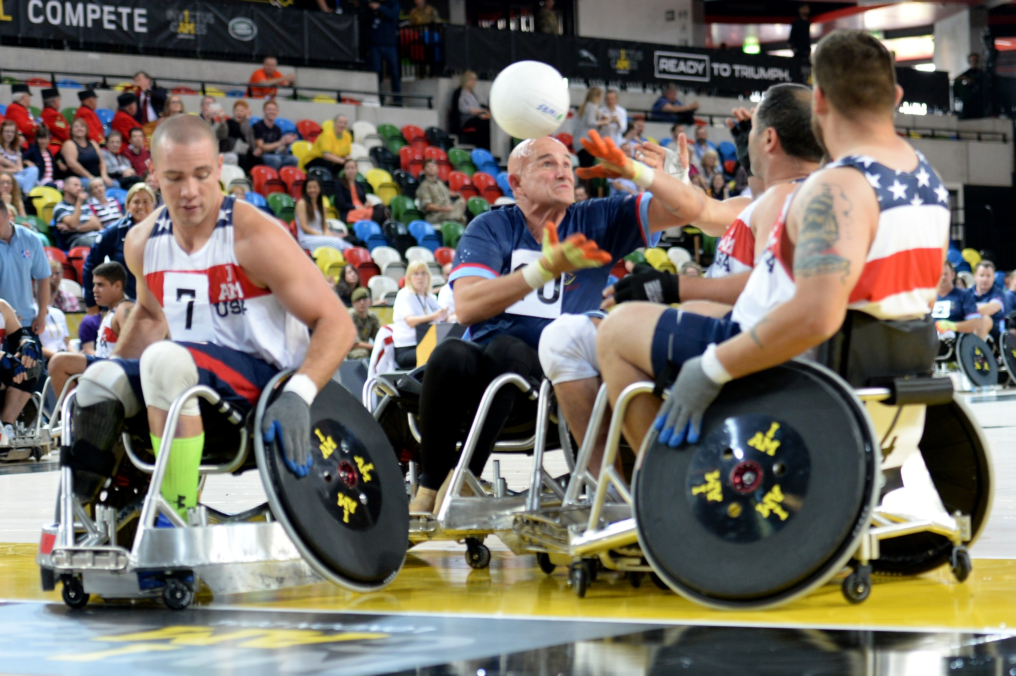 Three American defenders knock the ball away from an Australian player during a wheelchair rugby match Sept. 12, 2014, at the 2014 Invictus Games in London. The U.S. won the match 14-4. Invictus Games is an international competition that brings together wounded, injured and ill service members in the spirit of friendly athletic competition. American Soldiers, Sailors, Airmen and Marines are representing the U.S. in the competition which is taking place Sept. 10-14. (U.S. Navy photo/Mass Communication Specialist 2nd Class Joshua D. Sheppard)