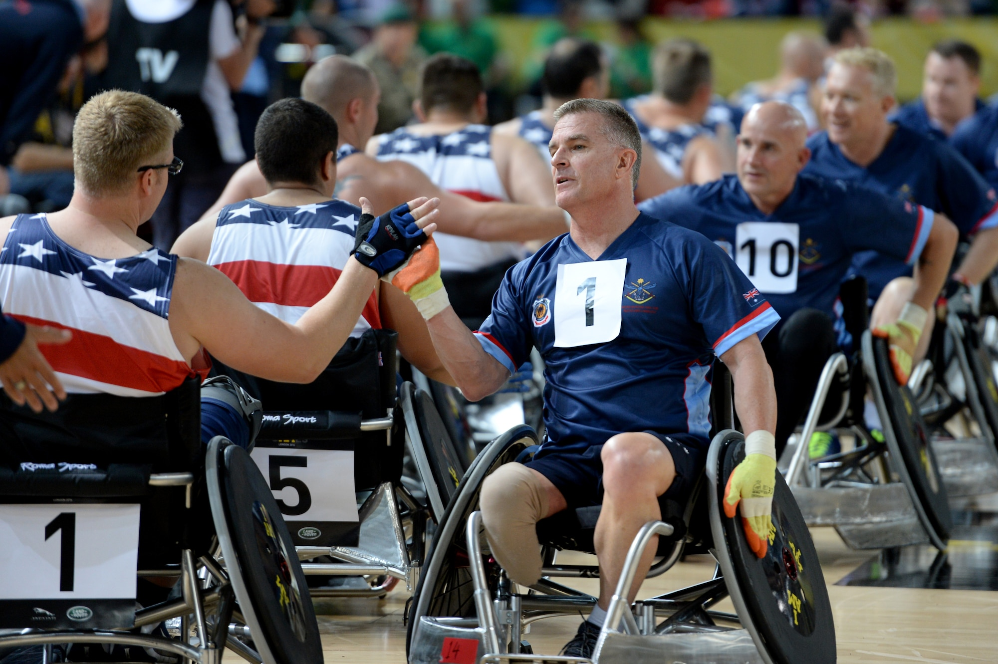 Members of the American and Australian wheelchair rugby teams congratulate each other after the U.S's 14-4 victory over Australia Sept. 12, 2014, at the 2014 Invictus Games in London. Invictus Games is an international competition that brings together wounded, injured and ill service members in the spirit of friendly athletic competition. American Soldiers, Sailors, Airmen and Marines are representing the U.S. in the competition which is taking place Sept. 10-14. (U.S. Navy photo/Mass Communication Specialist 2nd Class Joshua D. Sheppard)