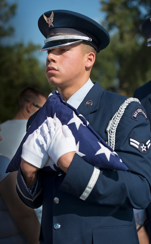 Airman 1st Class Gabriel Hurtado, 60th Aerial Port Squadron, carries a folded American Flag during a Freedom Walk Sept. 11, 2014, at Travis Air Force Base, Calif. (U.S. Air Force photo by Heide Couch)
