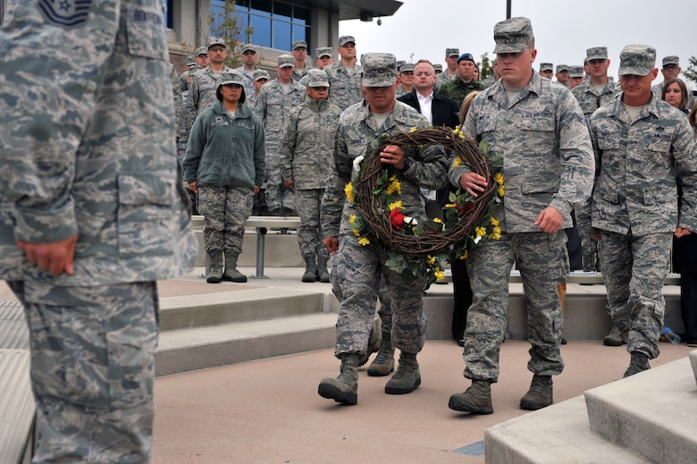 Airman 1st Class Ryan Mullen, 460th Operations Group administrator, right, and Senior Airman Matthew Greger, 2nd Space Warning Squadron, left, present the wreath during the Patriot Day retreat ceremony Sept. 11, 2014, on Buckley Air Force Base, Colo. Patriot Day is the national day of service and remembrance, in memory of the thousands killed on U.S. soil in the 9/11 attacks. (U.S. Air Force Photo by Airman Emily E. Amyotte/Released)