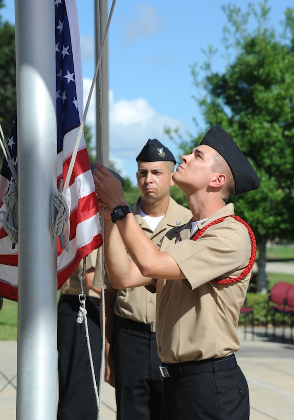 Seaman Grant Bradley, Center for Naval Aviation Technical Training Unit Keesler, raises the flag to half-mast as Petty Officer 1st Class Brian Draper, CNATTU, stands by during a remembrance ceremony Sept. 11, 2014, Keesler Air Force Base, Miss. The ceremony honored those who lost their lives during the 9/11 attacks. (U.S. Air Force photo by Kemberly Groue)